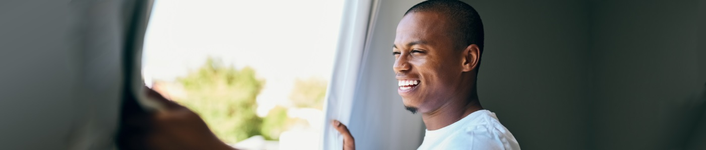 man waking and looking out of the window