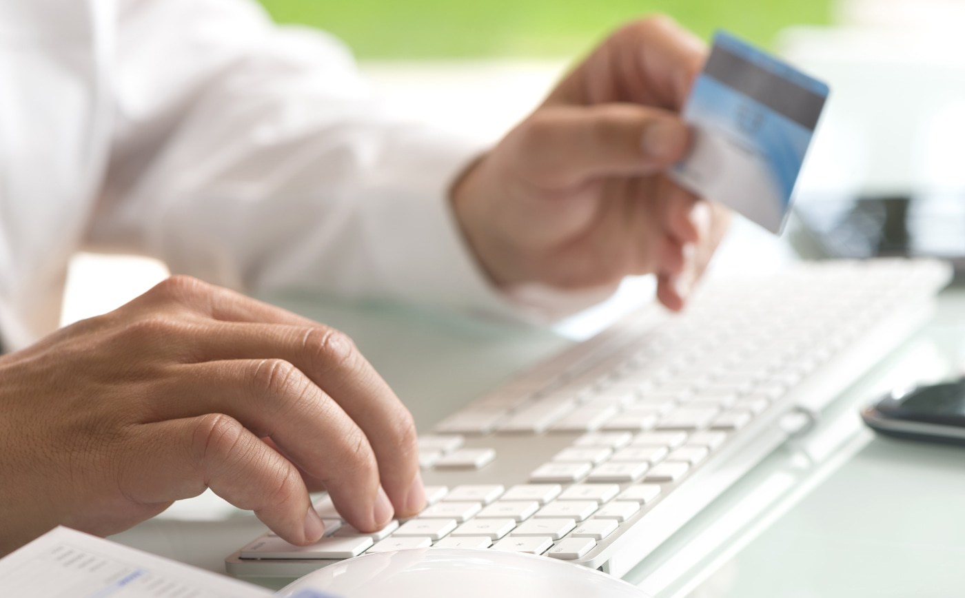 person typing on keyboard while holding a credit card