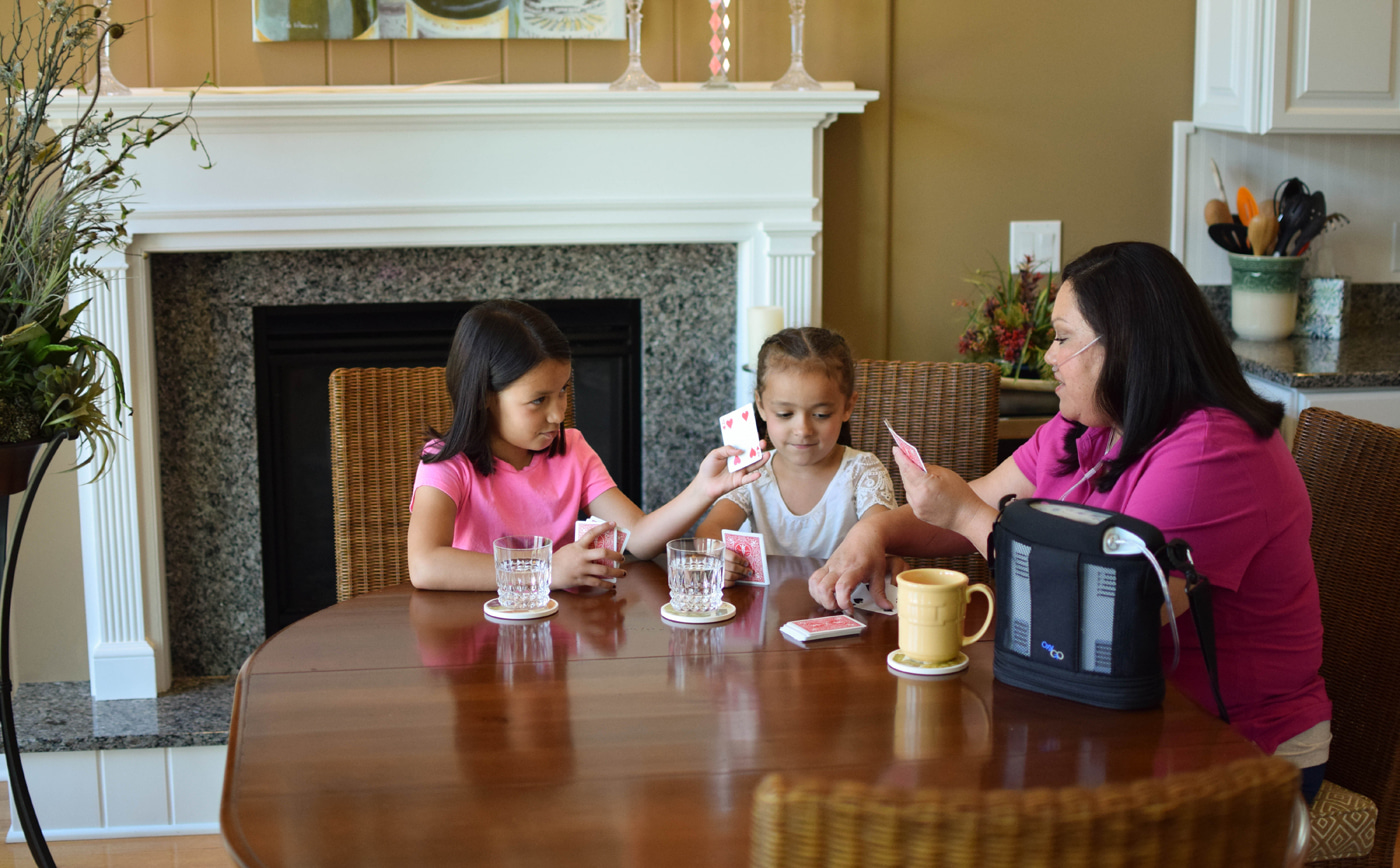 Grandmother playing cards with granddaughters while using the OxyGo